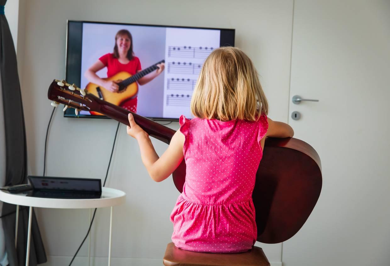 Une enfant apprenant la guitare
