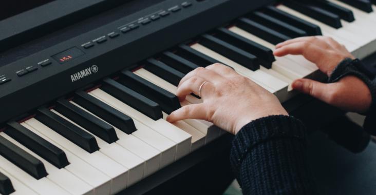 Un apprenti joue du piano numérique Yamaha